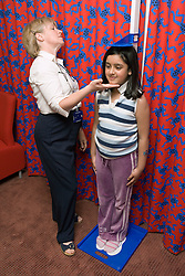 School nurse measuring height of young girl,