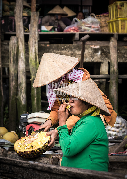 Two women eating Jackfruit on their boats at Phong Dien Floating Market on the Can Tho River in the Mekong Delta region of Vietnam