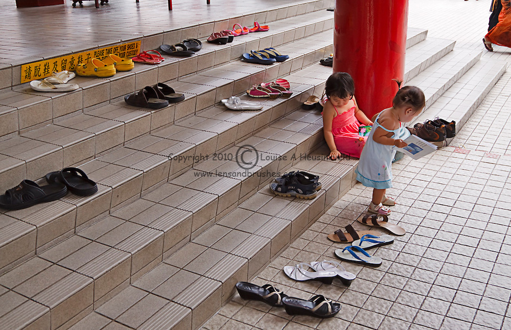 Small children await their parents at the Thean Hou Temple, Kuala Lumpur, Malaysia.  Shoes must be removed before entering the main part of the temple.