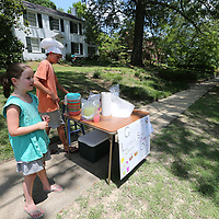 Celia Johnston, 7, left, and Grady Bartlett, 12, try their hand selling lemonade at Barlett's grandmother's nouse on Jefferson Street Monday. Barlett was trying to raise enough money to buy a new video game and give the rest to a local charity.