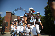 09/20/2014 - Somerville, Mass. - The football team makes its way through the Ellis Oval arch before facing Hamilton at Zimman Field on Sept. 20, 2014. (Kelvin Ma/Tufts University)