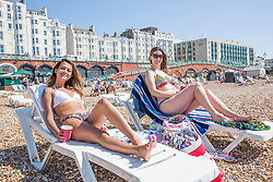 © Licensed to London News Pictures. 07/05/2018. Brighton, UK. (L to R) 36 year old MIRIAN LIMA and 37 year old SILVANIA SIMAO from Brazil spent the day on Brighton and Hove beach on the May Bank Holiday Monday as warm weather continues to hit the seaside resort. This weekend has been the hottest May Bank Holiday weekend on record. Photo credit: Hugo Michiels/LNP
