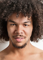 Clsoe-up portrait of a trendy young man with curly hair over white background.