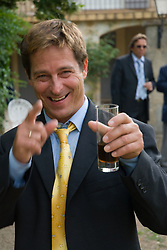 Man holding a drink in his hand enjoying himself at a party