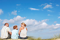 Father and mother sitting with son on sand dune back view