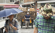 A South Korean elderly man pushes a cart containing waste papers which he collected to sell, on the way to a rag-and-bone merchant as it rains in Seoul, South Korea on July 17, 2017. Photo by Lee Jae-Won (SOUTH KOREA) www.leejaewonpix.com