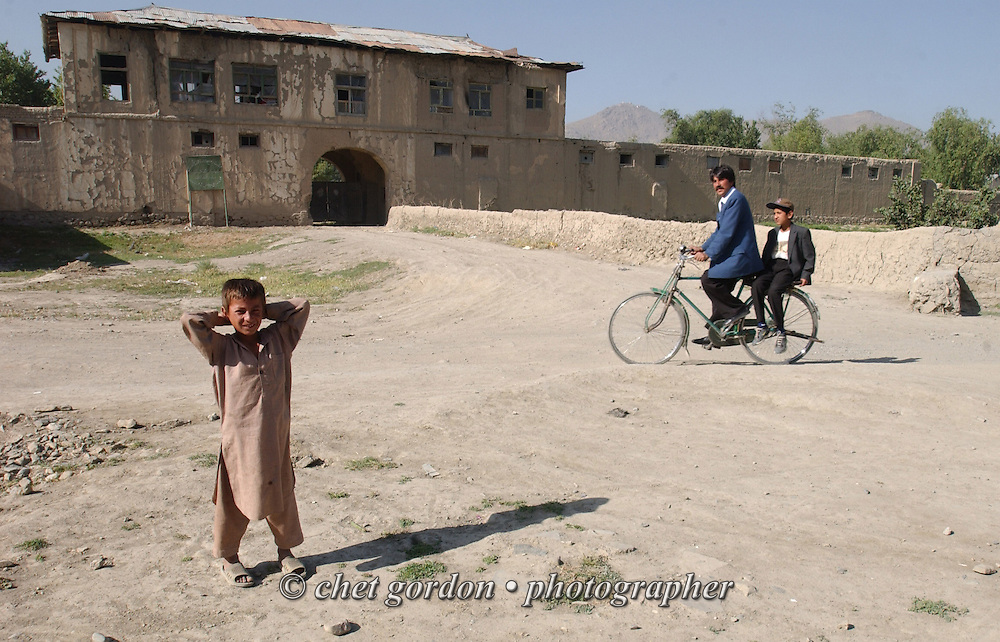Young boy and a bicyclist in a neighborhood back street in Kabul, Afghanistan on Sunday, May 26, 2002.