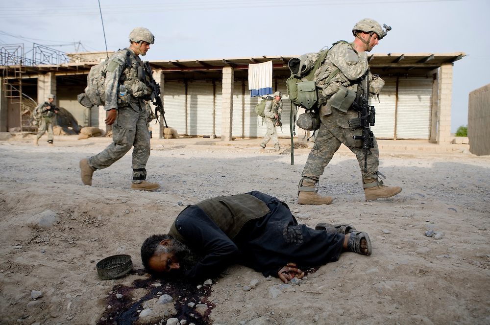 The 82nd Airborne's 1/508, Alpha Co., Third Platoon walks past a dead Afghan shot by British troops in Sangin, Helmand province, Afghanistan on Saturday, April 7, 2007.