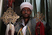 An Orthodox Christian priest holds golden crosses from one of the rock-hewn churches in Lalibela. Declared a UNESCO World Heritage Site, Lalibela's rock-hewn churches were built in the 12th and 13th centuries and are said to represent a miniature version of Jerusalem. Located at 2,500 meters above sea level, Lalibela is one of Ethiopia's holiest cities and a center of pilgrimage for the Ethiopian Orthodox Christian population. Lalibela, Amhara Division, Ethiopia. March 31, 2011.