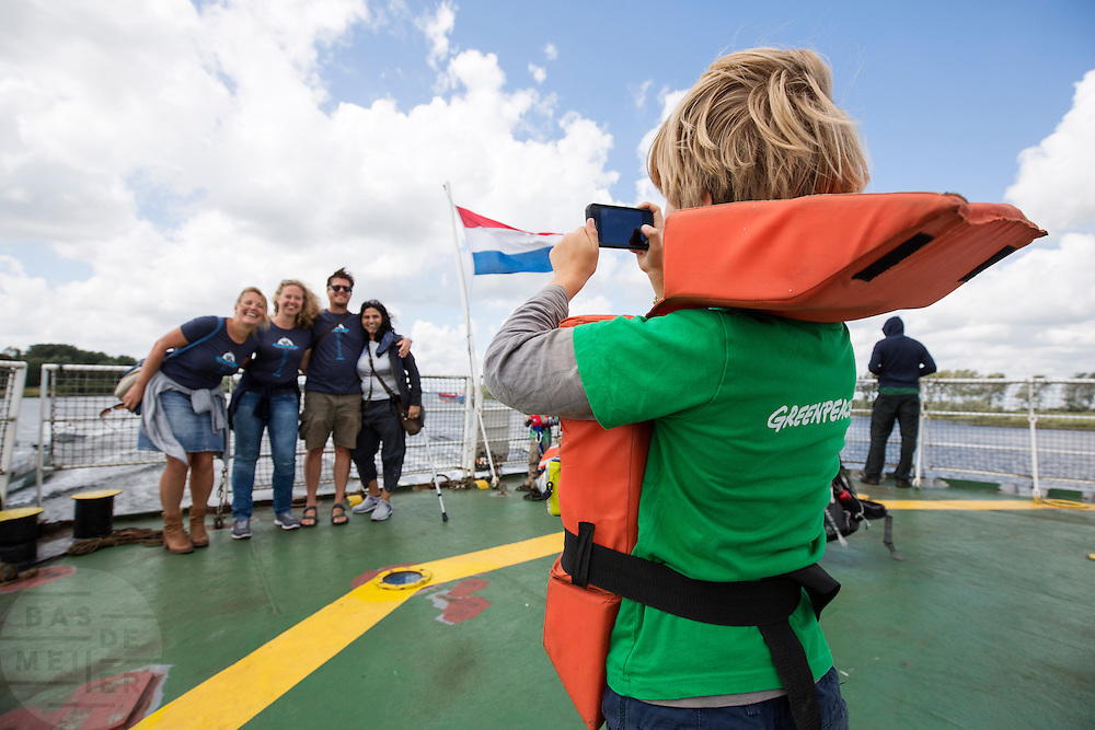 Een jongetje aan boord van de Arctic Sunrise maakt een foto van andere passagiers. In IJmuiden is de Arctic Sunrise, het schip van milieuorganisatie Greenpeace dat een jaar door Rusland in beslag is genomen, aangekomen. De voormalige ijsbreker wordt in Amsterdam uit het water gehaald en opgeknapt omdat het gehavend is geraakt toen het aan de ankers lag. De boot van de milieuorganisatie is september 2013 door de Russen geënterd en de bemanningsleden vastgezet op verdenking van piraterij. Greenpeace voerde actie bij een boorplatform in de Barentszzee. Als het schip weer is gerepareerd, wil de milieubeweging weer campagnes houden met de Artic Sunrise.<br /> <br /> In IJmuiden, the Arctic Sunrise, the Greenpeace ship that a year ago is seized by Russia, arrived. The former ice breaker is removed from the water in Amsterdam and refurbished since it was damaged when it was up to the anchors. The boat of the environmental organization is boarded in September 2013 by the Russians and the crew put down on suspicion of piracy. Greenpeace campaigned on a drilling platform in the Barents Sea. If the ship is repaired, the environmental movement wants to use the Arctic Sunrise again for campaigning.