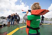 Een jongetje aan boord van de Arctic Sunrise maakt een foto van andere passagiers. In IJmuiden is de Arctic Sunrise, het schip van milieuorganisatie Greenpeace dat een jaar door Rusland in beslag is genomen, aangekomen. De voormalige ijsbreker wordt in Amsterdam uit het water gehaald en opgeknapt omdat het gehavend is geraakt toen het aan de ankers lag. De boot van de milieuorganisatie is september 2013 door de Russen ge&euml;nterd en de bemanningsleden vastgezet op verdenking van piraterij. Greenpeace voerde actie bij een boorplatform in de Barentszzee. Als het schip weer is gerepareerd, wil de milieubeweging weer campagnes houden met de Artic Sunrise.<br /> <br /> In IJmuiden, the Arctic Sunrise, the Greenpeace ship that a year ago is seized by Russia, arrived. The former ice breaker is removed from the water in Amsterdam and refurbished since it was damaged when it was up to the anchors. The boat of the environmental organization is boarded in September 2013 by the Russians and the crew put down on suspicion of piracy. Greenpeace campaigned on a drilling platform in the Barents Sea. If the ship is repaired, the environmental movement wants to use the Arctic Sunrise again for campaigning.