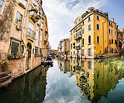 Yellow building reflects in Venice canals. Venice (Venezia), founded in the 400s AD, is capital of Italy's Veneto region, named for the ancient Veneti people from the 900s BC. The romantic City of Canals stretches across 100+ small islands in the marshy Venetian Lagoon along the Adriatic Sea, between the mouths of the Po and Piave Rivers. The Republic of Venice was a major maritime power during the Middle Ages and Renaissance, a staging area for the Crusades, and a major center of art and commerce (silk, grain and spice trade) from the 1200s to 1600s. The wealthy legacy of Venice stands today in a rich architecture combining Gothic, Byzantine, and Arab styles. Venice and the Venetian Lagoon are honored on UNESCO's World Heritage List. This image was stitched from 15 overlapping photos.