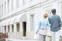 Rear view of middle-aged couple walking by building