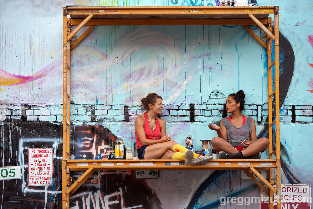 Alejandra Soler and Maria Ayala take a break during the Freak Alley Gallery sixth annual mural event in downtown Boise, Idaho on August 8, 2016. <br /> <br /> Their mural features four female forms as representations of the four elements; water, air, earth, and fire.<br /> <br /> The week long event provided an &quot;art-in-motion&quot; experience as it welcomed the public to watch artists work on their murals.