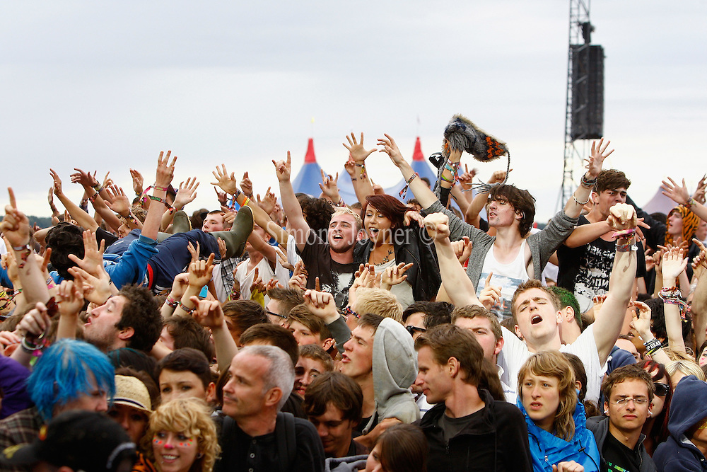 Music fans sit on each other's shoulder as Enter Shikari performs live on the Main Stage during day three of Reading Festival 2011 on August 28, 2011 in Reading, England.  (Photo by Simone Joyner)