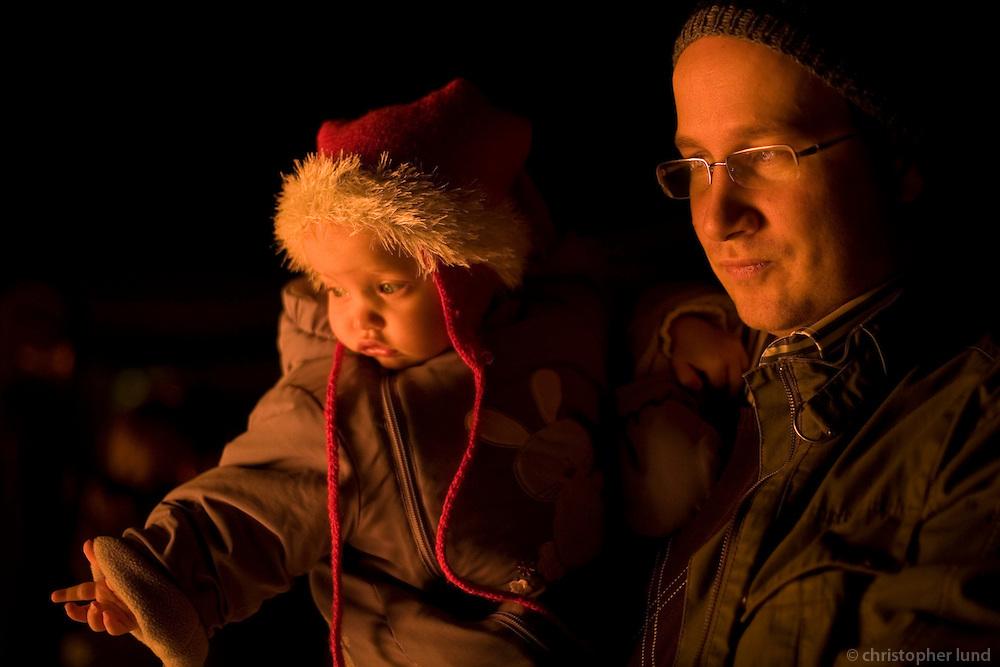 A father with his baby daugher looking towards a fire. Warm light in their faces...Á Þrettándabrennu. Andri Snær með Elínu Freyju.