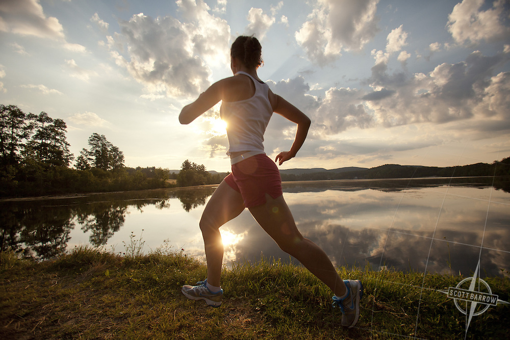 Twenty year old woman running at dawn/dusk past a crystal clear lake.