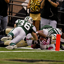 2009 October 04: New Orleans Saints running back Pierre Thomas (23) is tackle by New York Jets linebacker David Harris (52) and safety Jim Leonhard (36) during a 24-10 win by the New Orleans Saints over the New York Jets at the Louisiana Superdome in New Orleans, Louisiana.
