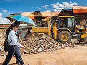 02 AUGUST 2015 - BHAKTAPUR, NEPAL:  People in Bhaktapur walk past a crew removing debris from the earthquake that hit Nepal in April 2015. Bhaktapur was badly damaged in the earthquake the hit Nepal in April 2015. The Nepal Earthquake on April 25, 2015, (also known as the Gorkha earthquake) killed more than 9,000 people and injured more than 23,000. It had a magnitude of 7.8. The epicenter was east of the district of Lamjung, and its hypocenter was at a depth of approximately 15 km (9.3 mi). It was the worst natural disaster to strike Nepal since the 1934 Nepal–Bihar earthquake. The earthquake triggered an avalanche on Mount Everest, killing at least 19. The earthquake also set off an avalanche in the Langtang valley, where 250 people were reported missing. Hundreds of thousands of people were made homeless with entire villages flattened across many districts of the country. Centuries-old buildings were destroyed at UNESCO World Heritage sites in the Kathmandu Valley, including some at the Kathmandu Durbar Square, the Patan Durbar Squar, the Bhaktapur Durbar Square, the Changu Narayan Temple and the Swayambhunath Stupa. Geophysicists and other experts had warned for decades that Nepal was vulnerable to a deadly earthquake, particularly because of its geology, urbanization, and architecture.      PHOTO BY JACK KURTZ