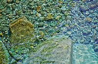 Crystal clear water flowing over smooth stones forms a beautiful green colored background.