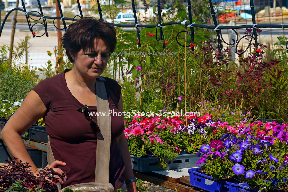 Female customer in a nursery. having a difficult trying to choose the right flowers for her garden the plants and flowers can be seen around the client