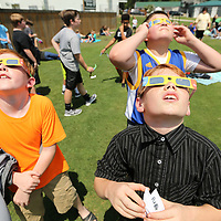 Mooreville Middle School students Peyton Reed, Alexander Dukes, and Logan Blanchard, back right, look up at the Solar Eclipse as the entire Middle School spent time on Monday afternoon on the baseball field to view the event.
