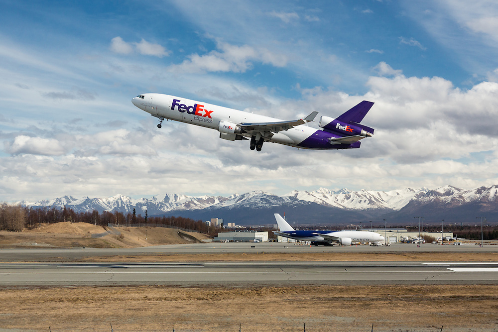 FedEx cargo jet taking off from Ted Stevens Anchorage International Airport in Southcentral Alaska with the Chugach Mountains in the background. Spring. Afternoon.