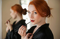 Portrait of a redheaded woman applying lip liner