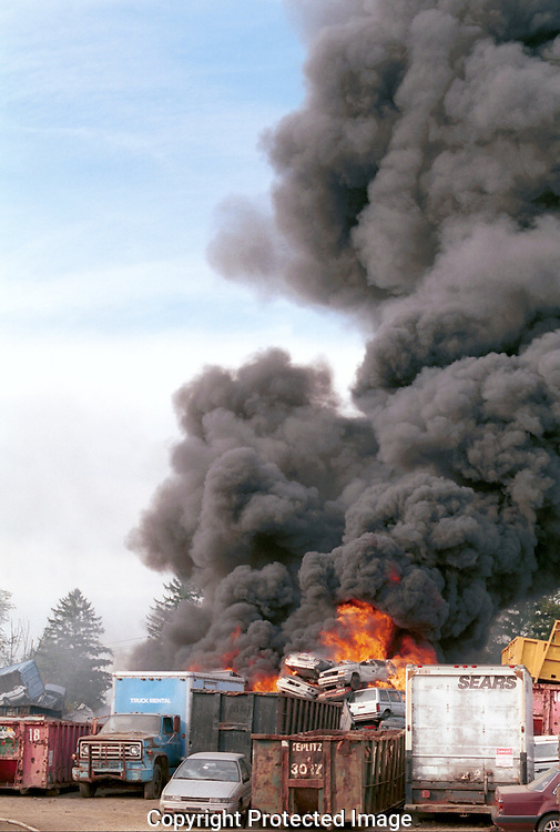 NANUET, NY - OCTOBER 9, 2003: Firefighters battle the flames that engulfed several cars at the Teplitz Junk Yard at 108 West Nyack Road October 9, 2013 in Nanuet, New York. Witnesses say the smoke could be seen from miles away. Several fire crews battled the blaze that burned for about an hour. Hazmat teams were called in to investigate. Fortunately, no one was hurt.