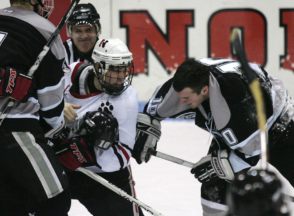(Boston, MA - 012409) - NEHOCK - Northeastern forward Ryan Ginand rips the helmet off Providence forward Austin Mayer during a fight in the first period. Ginand was responding to an open-ice hit by Mayer. Northeastern Huskies play Providence Friars in a Hockey East matchup at Matthews Arena Saturday. ..(012409nehock - Herald photo by Will Nunnally and edition)