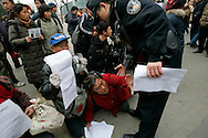 A Chinese Protester wrestles with police as she tries to retrieve  letters detailing her complaints and asks for justice outside of the Foreign Ministry  Beijing, China, Wednesday, Dec.10, 2008. Two dozen people held a bold protest using the 60th anniversary of the declaration of human rights to decry a myriad of alleged government abuses.(AP Photo/ Elizabeth Dalziel)
