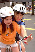 Police officer helping girl at Youth Express Bicycle Safety Rodeo age 35 and 6.  St Paul  Minnesota USA