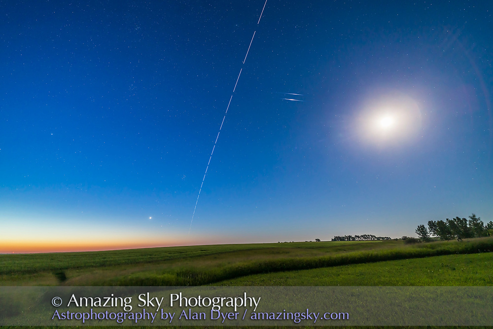 The International Space Station in a dawn pass, as it flies away to the east after passing overhead. This was the morning of July 15, 2017. <br /> <br /> Blended in are images taken 20 minutes later of a pair of Iridium satellite flares in the dawn, the one below (Iridium 54) being the first to appear, at a predicted magnitude of -7, while the one above (Iridium 90) appeared one minute later at magnitude -3. <br /> <br /> Venus is the bright object at lower left in the dawn twilight above Aldbaran and below the Pleaides. Capella is at far left. The waning Moon is overexposed at far right.  <br /> <br /> This is a bit of cheat as the Iridiums were taken later than the ISS shots, but with the camera not moved and shooting a time-lapse through the entire sequence, from ISS appearance until the expected Iridium appearances later. The sky for the Iridiums was brighter and bluer than for the ISS set, so that had to be corrected for in brightness and selective colour adjustments. <br /> <br /> This is a useful image for comparing the ISS and Iridiums to Venus for brightness. However, by the time the ISS got into the east here, it had dimmed quite a bit from its peak in brightness overhead. <br /> <br /> The set for the Iridiums is a composite of 8 exposures, all 10 second exposures at f/2.5 with the Rokinon 14mm SP and Canon 6D. <br /> <br /> The set for the ISS trail is a composite stack of 24 exposures for the ISS, masked onto a single background image of the sky taken just before the ISS entered the frame. This kept the stars as points rather than trails, while the ISS trailed across the sky. The gaps are from the 2 second interval between 10-second exposures. All with the Canon 6D and 14mm Rokinon lens at f/2.5.