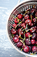 Washed fresh cherries in a colander.