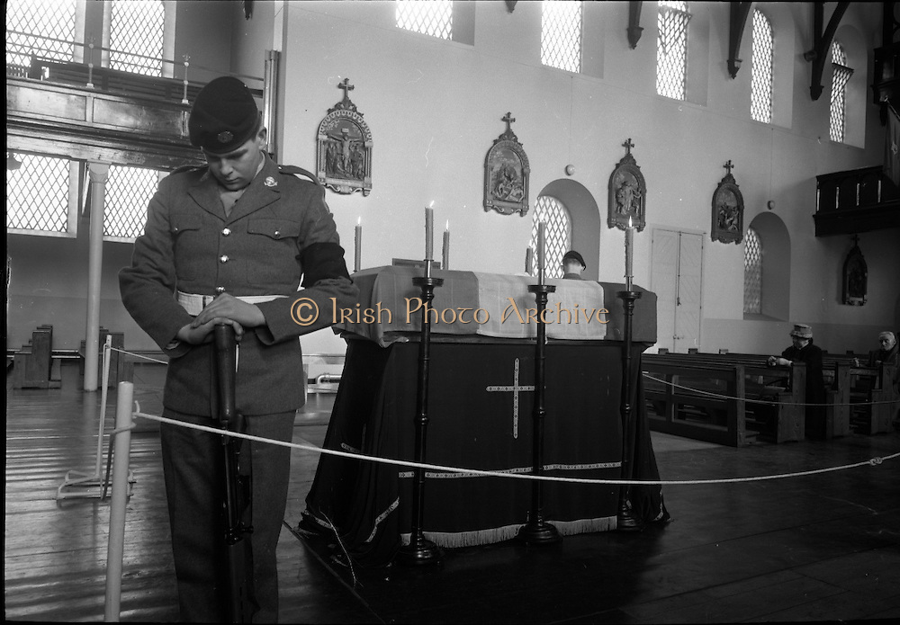 Roger Casement lies in State in Dublin.  An Irish soldier stands with head bowed at the tricolour draped coffin of Roger Casement at the Military Church at Arbour Hill..24.02.1965