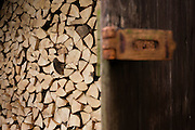 Piles of sawn logs and padlock, ready for a winter home fire, stays dry under cover on a small holding.