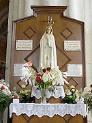 devotional altar with a Maria statue and flowers in a church