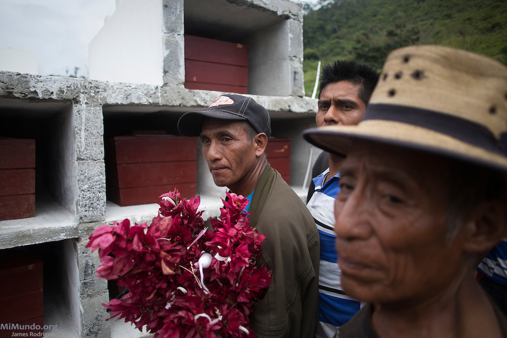 Bernardo de Paz Lopez (left), 46, listens as friends and family bury the human remains of twenty-six identified war victims killed either in 1982 or 1985, including his sister Maria de Paz Lopez (3-years-old at the time of her killing), and grandparents Fernando de Paz and Petrona Paiz (both 60 at the time of their killing). The war victims were exhumed from mass graves by members of the Forensic Anthropology Foundation of Guatemala (FAFG) in 2006 and returned for a proper burial nearly a decade later. The village of Xecoyeu is a community founded in the early 1980s by Ixil Mayans displaced by the violence in their communities due to State repression that included dozens of massacres of entire villages as a way to demoralize leftist guerrillas operating in the region. Xecoyeu, Chajul, Quiché, Guatemala. October 7, 2016.