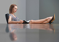 Businesswoman sitting and studying book feet on table side view