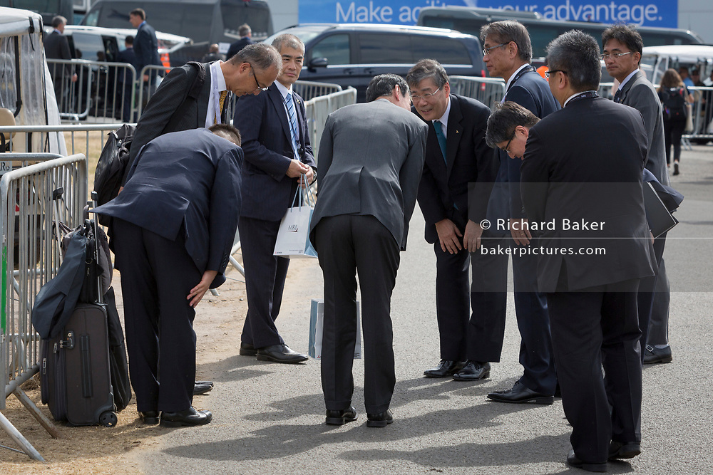 Japenses businessmen bow to each other after a day at the Farnborough Airshow, on 16th July 2018, in Farnborough, England. (Photo by Richard Baker / In Pictures via Getty Images)