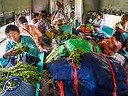 26 OCTOBER 2015 - YANGON, MYANMAR: The crowded Yangon Circular Train. The Yangon Circular Railway is the local commuter rail network that serves the Yangon metropolitan area. Operated by Myanmar Railways, the 45.9-kilometre (28.5 mi) 39-station loop system connects satellite towns and suburban areas to the city. The railway has about 200 coaches, runs 20 times daily and sells 100,000 to 150,000 tickets daily. The loop, which takes about three hours to complete, is a popular for tourists to see a cross section of life in Yangon. The trains run from 3:45 am to 10:15 pm daily. The cost of a ticket for a distance of 15 miles is ten kyats (~nine US cents), and for over 15 miles is twenty kyats (~18 US cents).    PHOTO BY JACK KURTZ