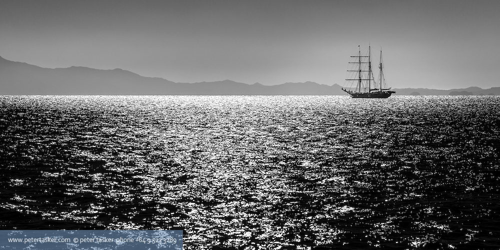 Tall ship, 'Spirit of New Zealand' at anchor in Hooks Bay Waihehe Island.  Coromandel Peninsular in the background.  Early morning light.