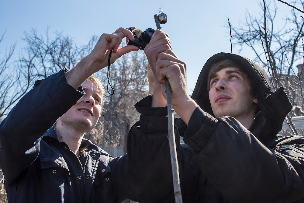 LUHANSK, UKRAINE - MARCH 16, 2015: Aleksandr Kryukov, left, photographs a lightbulb held by Pavel Pavlov which broke after being exposed to microwaves in the yard of the house where Kryukov lives with his grandmother in Luhansk, Ukraine. The two have created a series of popular YouTube videos involving scientific experiements. CREDIT: Brendan Hoffman for The New York Times
