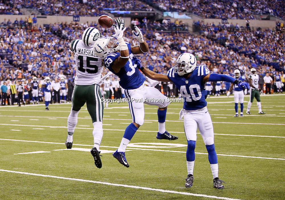 Indianapolis Colts free safety Dwight Lowery (33) and Indianapolis Colts cornerback Sheldon Price (40) leap with outstretched arms as they break up a deep pass intended for New York Jets wide receiver Brandon Marshall (15) during the 2015 NFL week 2 regular season football game against the New York Jets on Monday, Sept. 21, 2015 in Indianapolis. The Jets won the game 20-7. (©Paul Anthony Spinelli)