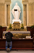 A visitor kneels in prayer before a statue of Jesus at the Cathedral-Basilica of Notre-Dame de Québec. (Photo by Sam Lucero)