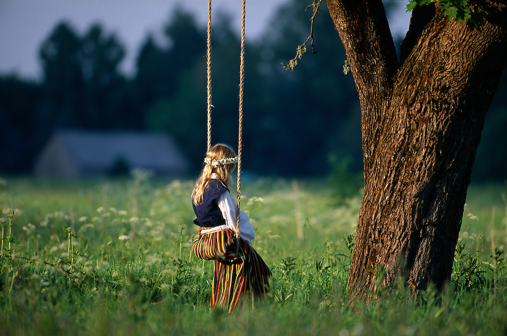 Young Estonian girl in traditional costume sitting on a swing