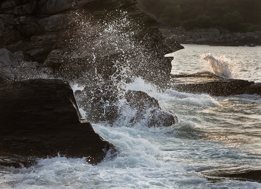 Fast shutter speed captures crashing waves along the rocky coast of Maine, Portland Head