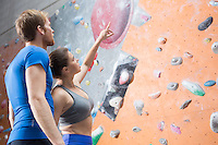 Friends discussing by climbing wall in crossfit gym