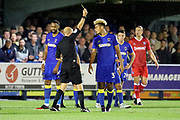 AFC Wimbledon striker Lyle Taylor (33) yellow card during the EFL Sky Bet League 1 match between AFC Wimbledon and Gillingham at the Cherry Red Records Stadium, Kingston, England on 12 September 2017. Photo by Matthew Redman.