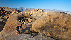 Photographer standing next to the Alabama Hills Arch, Lone Pine, California, United States of America